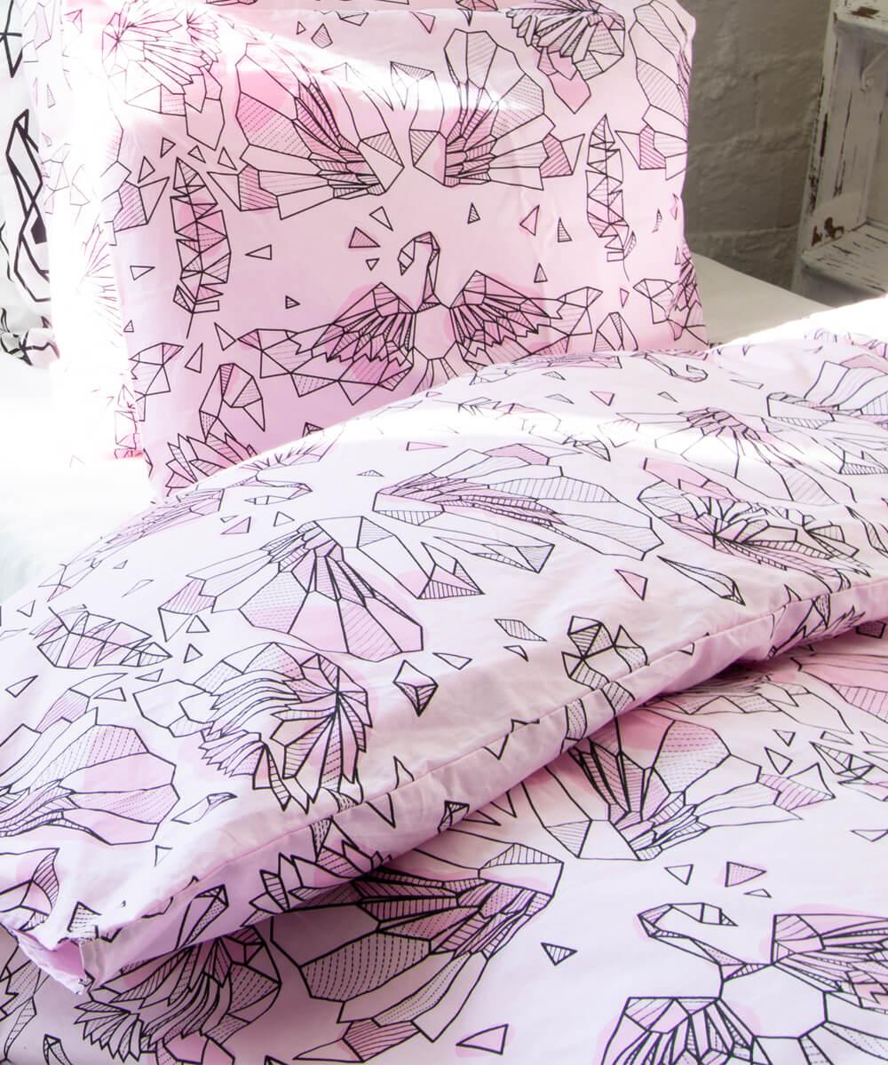 Graafinen joutsenkuvio vaalenpunaisessa pussilakanassa ja tyynyliinassa.