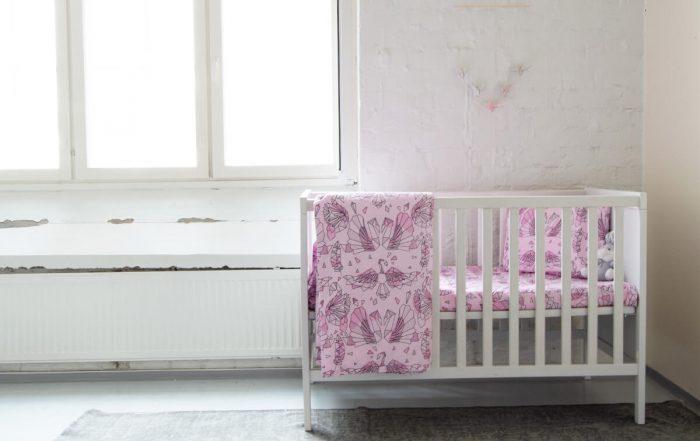 Vaaleanpunainen vauvan pussilakanasetti pinnasänkyyn.