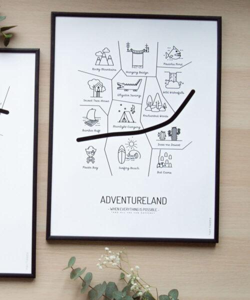 Mustavalkoinen ADVENTURELAND -lastenhuoneen juliste kehystettynä.