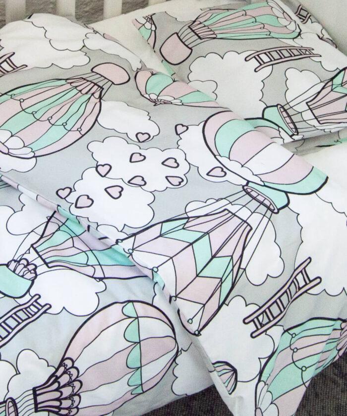 Luomupuuvillainen vauvan pussilakanasetti, jossa kuumailmapalloja ja sydämiä.