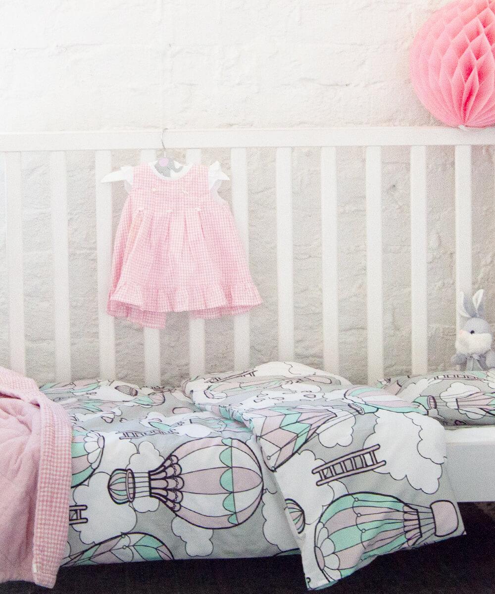 Mintunvihreä ja vaaleanpunainen pussilakanasetti vauvalle, jossa on kuumailmapalloja, pilviä ja sydämiä.