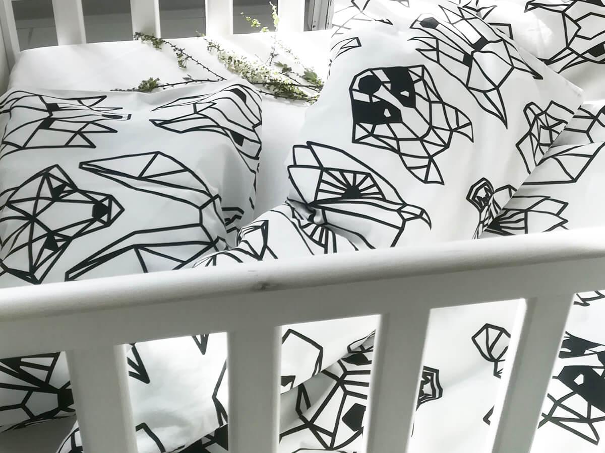 Mustavalkoinen vauvan pussilakanasetti pinnasängyssä