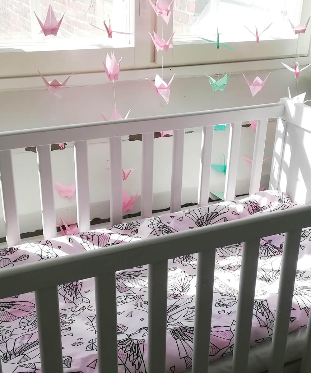 Herkkä vaaleanpunainen pussilakanasetti vauvalle, jossa on graafisena kuviona jousenia ja höyheniä.