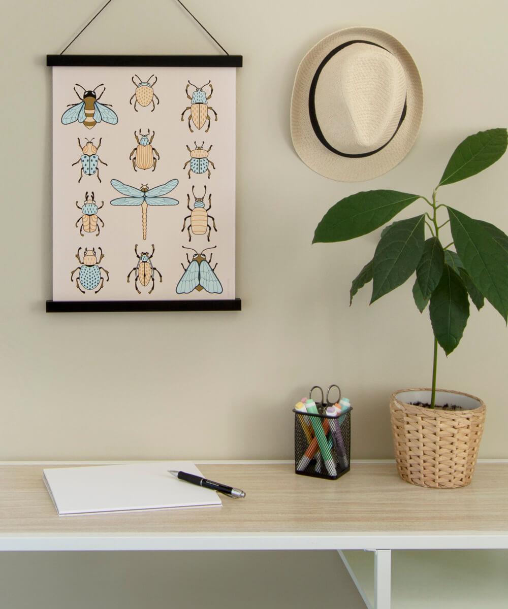 Söpö hyönteisjuliste ripustettuna kirjoituspöydän yläpuolelle.