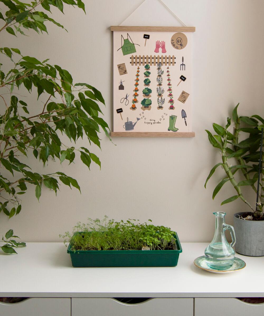 Söpö puutarhanhoitojuliste ripustettuna kasvipöydän yläpuolelle.