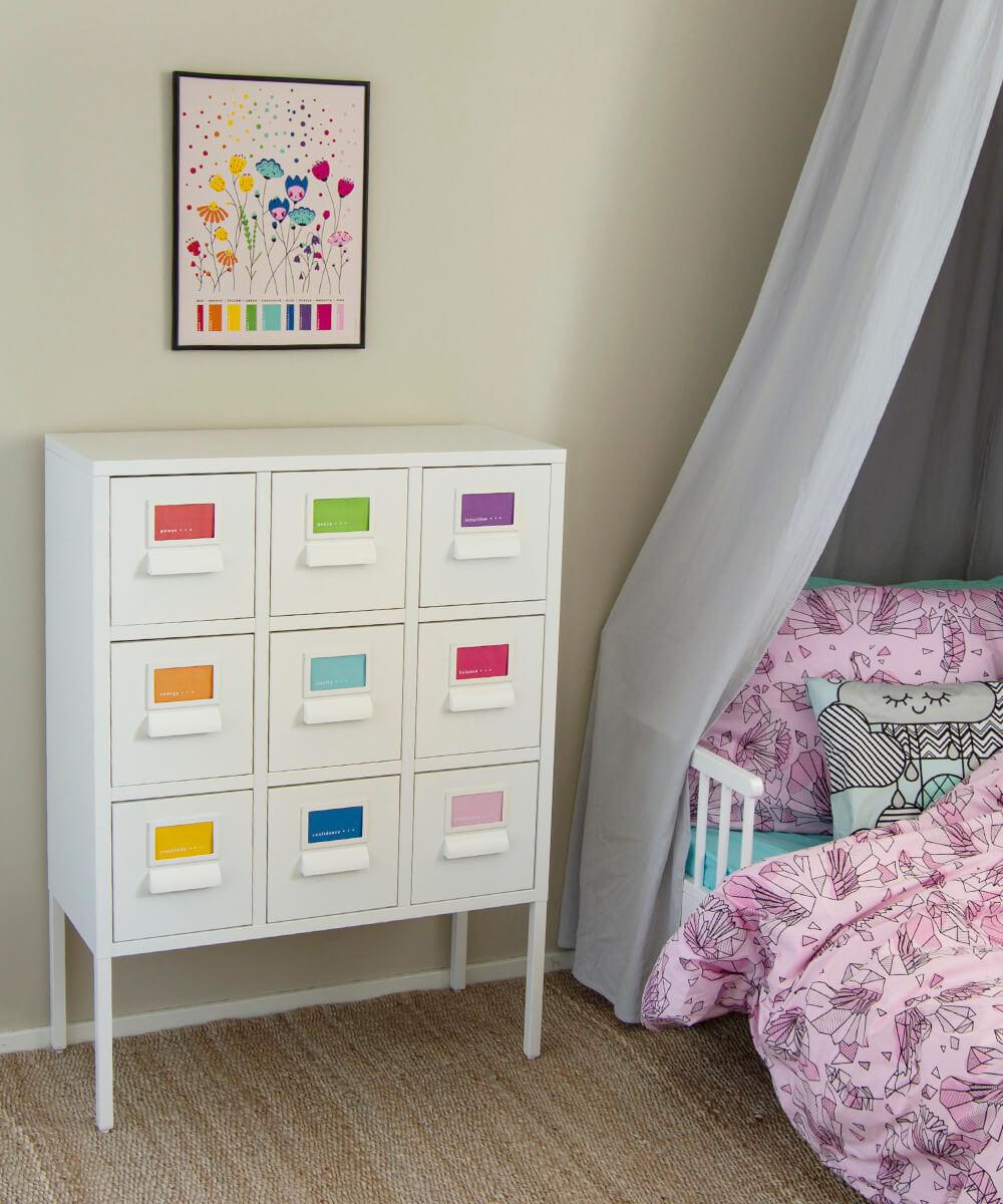 Kirkkaan värikäs lastenhuoneenjuliste, lipasto ja vaaleanpunaiset lakanat.